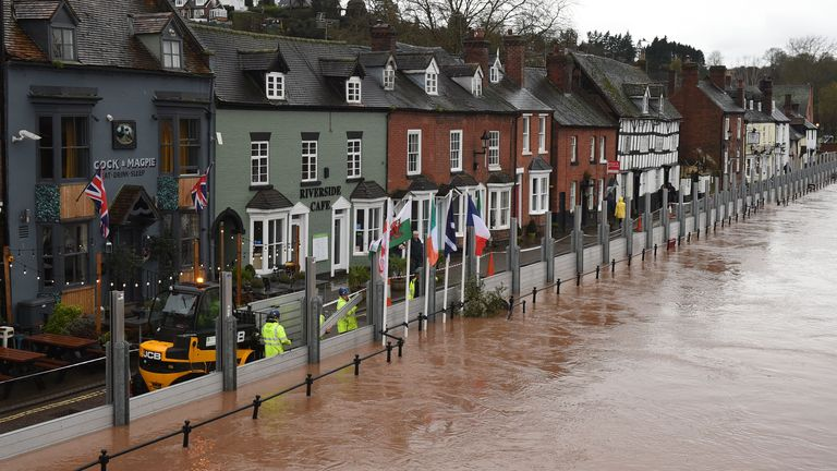 "Environment agency workers puts up flood defences beside the River Severn in Bewdley, west of Birmingham on February 16, 2020, after Storm Dennis caused flooding across large swathes of Britain. - As Storm Dennis sweeps in, the country is bracing itself for widespread weather disruption for the second weekend in a row. Experts have warned that conditions amount to a ""perfect storm"", with hundreds of homes at risk of flooding. (Photo by Oli SCARFF / AFP) (Photo by OLI SCARFF/AFP via Getty Images)"