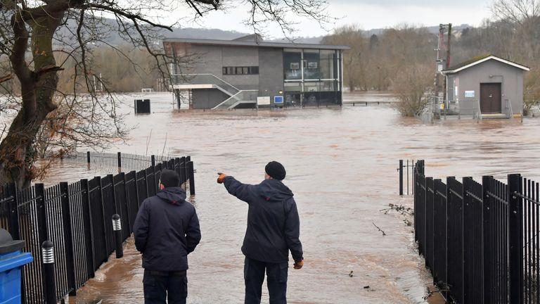 Two men view a flooded area of the sports pavilion at Monmouth School, Monmouth, in the aftermath of Storm Dennis.