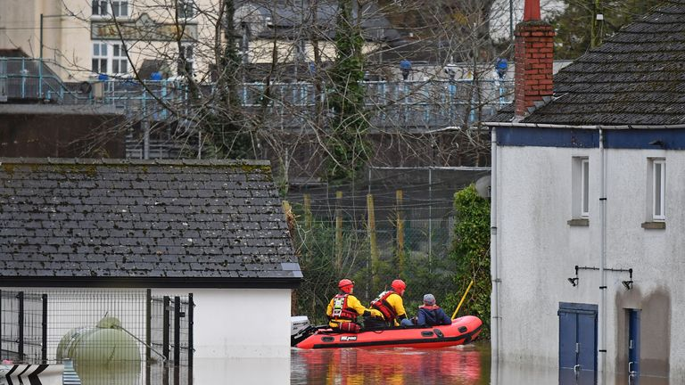 "South Wales Fire and Rescue take a resident through floodwaters in Monmouth, south Wales on February 18, 2020, after Storm Dennis caused flooding across large swathes of Britain. - People are being urged to leave their homes in the face of further flooding as one official warned residents are ""not out of the woods yet"" in the aftermath of Storm Dennis.  There were 10 severe flood warnings in place at one point across England and Wales, and warnings of continued problems amid a forecast of more heavy rain forecast later in the week. (Photo by Ben STANSALL / AFP) (Photo by BEN STANSALL/AFP via Getty Images)"