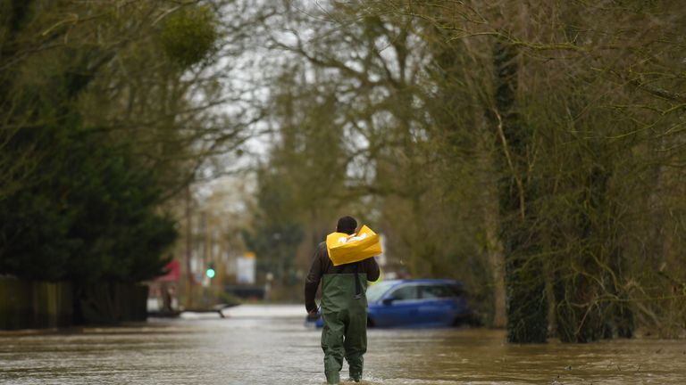 A man wades through flood water in Upton-upon-Severn, Worcestershire, in the aftermath of Storm Dennis.