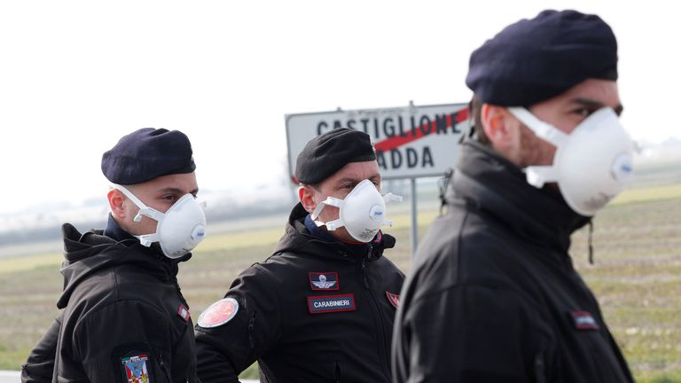 Carabinieri officers stand guard outside the town of Castiglione D'Adda, which has been closed by the Italian government due to a coronavirus outbreak, Italy, February 23, 2020. REUTERS/Guglielmo Mangiapane