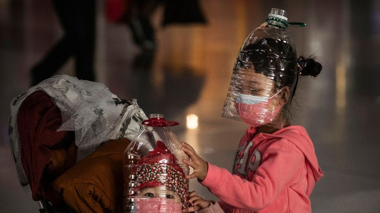 BEIJING, CHINA - JANUARY 30: Chinese children wear plastic bottles as makeshift homemade protection and protective masks while waiting to check in to a flight at Beijing Capital Airport on January 30, 2020 in Beijing, China. The number of cases of a deadly new coronavirus rose to over 7000 in mainland China Thursday as the country continued to lock down the city of Wuhan in an effort to contain the spread of the pneumonia-like disease which medicals experts have confirmed can be passed from human to human. In an unprecedented move, Chinese authorities put travel restrictions on the city which is the epicentre of the virus and neighbouring municipalities affecting tens of millions of people. The number of those who have died from the virus in China climbed to over 170 on Thursday, mostly in Hubei province, and cases have been reported in other countries including the United States, Canada, Australia, Japan, South Korea, and France. The World Health Organization  has warned all governments to be on alert, and its emergency committee is to meet later on Thursday to decide whether to declare a global health emergency. (Photo by Kevin Frayer/Getty Images)