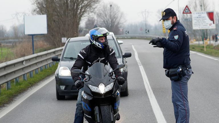 Policemen wearing face masks warn drivers on the road between Codogno and Casalpusterlengo, which has been closed by the Italian government due to a coronavirus outbreak in northern Italy, February 23, 2020. REUTERS/Guglielmo Mangiapane.