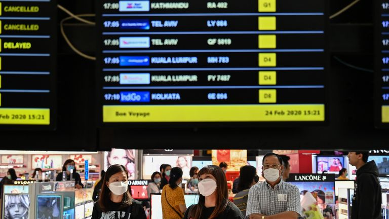 Passengers with protective masks look at a flights information board at Suvarnabhumi airport in Bangkok, on February 24, 2020. - The novel coronavirus has spread to more than 25 countries since it emerged in December and is causing mounting alarm due to new outbreaks in Europe, the Middle East and Asia. (Photo by Hector RETAMAL / AFP) (Photo by HECTOR RETAMAL/AFP via Getty Images)