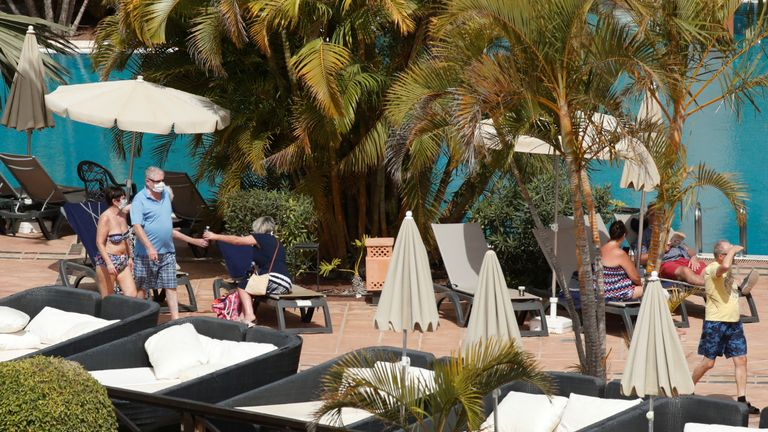 Tourists with masks are seen near the pool of H10 Costa Adeje Palace, which is on lockdown after cases of coronavirus have been detected there in Adeje, on the Spanish island of Tenerife, Spain, February 26, 2020. REUTERS/Borja Suarez