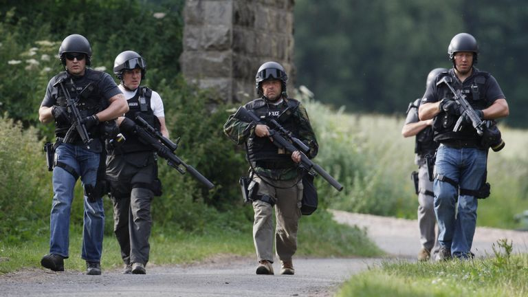 Armed police escort a man, hidden from view, as they escort him near to Wagtail Farm, Northumberland, as the manhunt for fugitive gunman Raoul Moat continues.