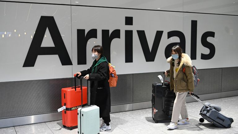 "Passengers wear face masks as the push their luggage after arriving from a flight at Terminal 5 of London Heathrow Airport in west London on January 28, 2020. - Chinese President Xi Jinping said Tuesday the country was waging a serious fight against the ""demon"" coronavirus outbreak and pledged transparency in the government's efforts to contain the disease. (Photo by DANIEL LEAL-OLIVAS / AFP) (Photo by DANIEL LEAL-OLIVAS/AFP via Getty Images)"