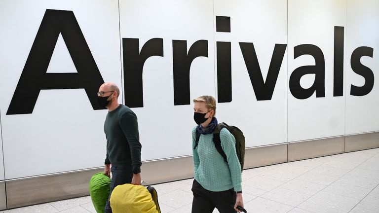 "Passengers wear face masks as they arrive with their luugage at Terminal 4 of London Heathrow Airport in west London on January 28, 2020. - Chinese President Xi Jinping said Tuesday the country was waging a serious fight against the ""demon"" coronavirus outbreak and pledged transparency in the government's efforts to contain the disease. (Photo by DANIEL LEAL-OLIVAS / AFP) (Photo by DANIEL LEAL-OLIVAS/AFP via Getty Images)"