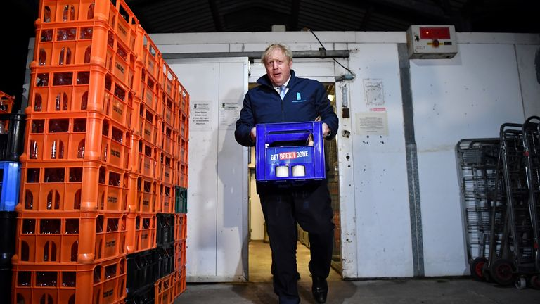 Britain's Prime Minister Boris Johnson carries a crate of milk to deliver to customers at Greenside Farm on the final day of campaigning before Thursday's general election on December 11, 2019 in Yeadon, near Leeds