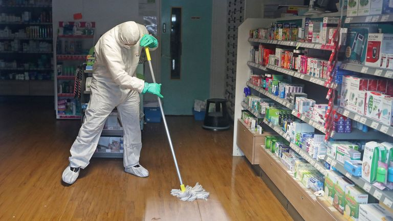 A man in protective clothing cleans the County Oak Medical Centre GP practice