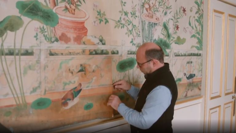 The wallpaper is being carefully removed piece-by-piece