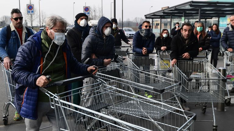 Residents wait to be given access to shop in a supermarket in small groups of forty people on February 23, 2020 in the small Italian town of Casalpusterlengo