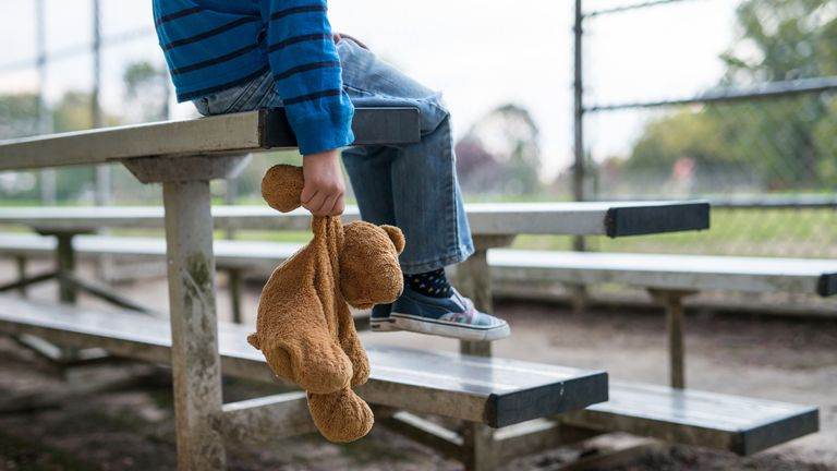 Young boy sitting by himself on bleachers and holding teddy bear.