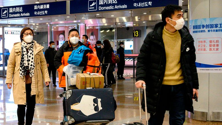 Passengers, wearing protective facemasks, walk at the arrival area of the Beijing Capital International airport
