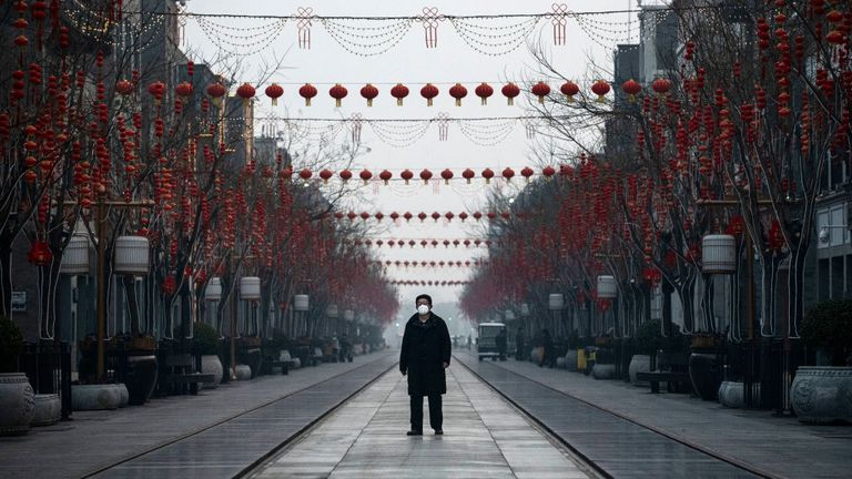Chinese man wears a protective mask as he walks in a nearly empty and shuttered commercial street on February 12, 2020 in Beijing, China