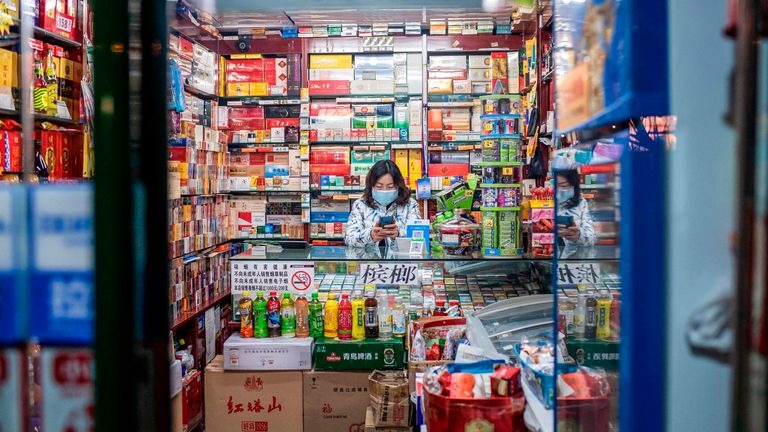 A woman waits for customers in a shop in Beijing