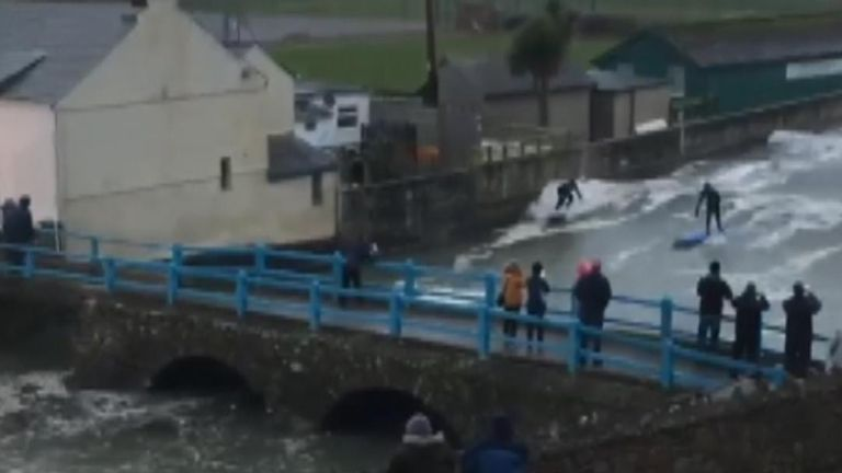 Surfers negotiate bridge as they ride waves along Cornwall river