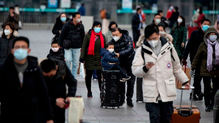 Mask-wearing passengers are seen leaving Beijing railway station