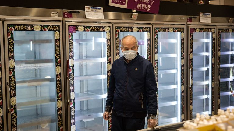 A man stands in front of empty supermarket shelves in Wuhan, the epicentre of the outbreak