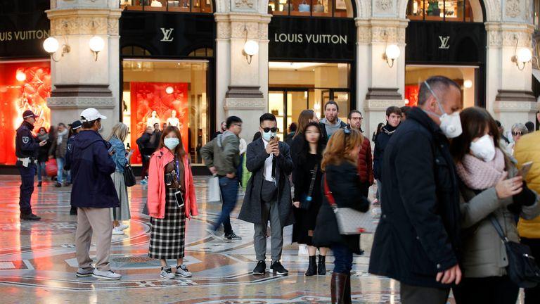 Tourists wearing sanitary masks walk in downtown Milan, Italy