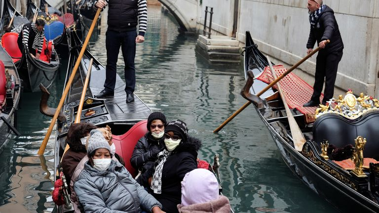 Tourists wear protective face masks in a gondola, because of an outbreak of coronavirus, in Venice, Italy February 23, 2020