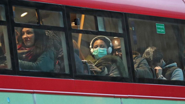 A woman wears a face mask on a bus in London