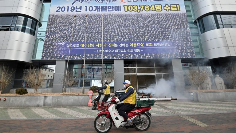 Disinfectant is sprayed in front of the Shincheonji Church of Jesus in Daegu