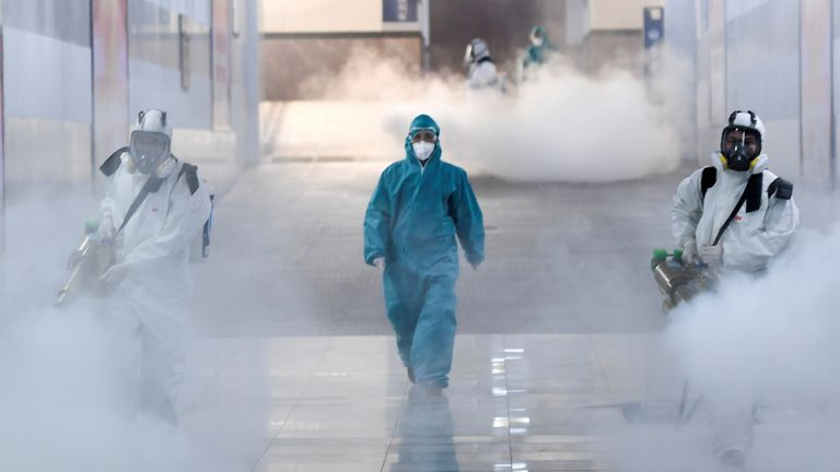 Volunteers in protective suits disinfect a railway station as the country is hit by an outbreak of the new coronavirus, in Changsha, Hunan province
