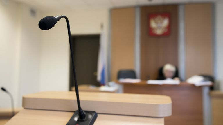 Wooden table in court of law with microphone and gavel