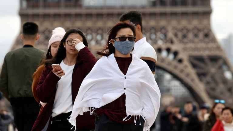 Tourists at the Eiffel Tower in Paris, as France confirms its first coronavirus death. File picture