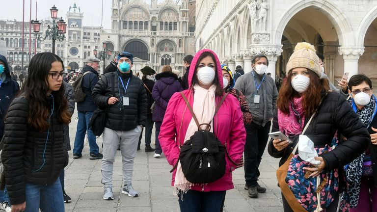 Tourists wear protective masks in Venice after the city's carnival was cancelled due to COVID-19