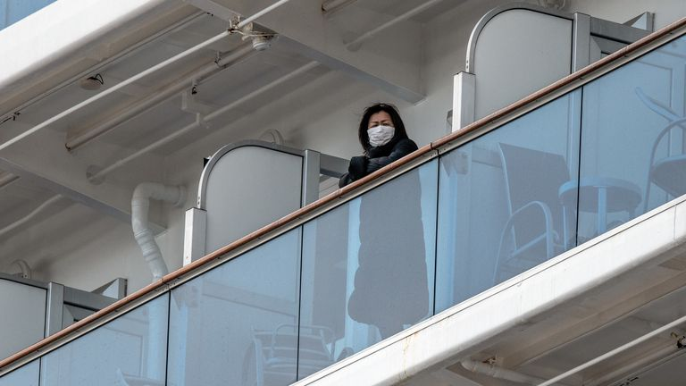 Passengers onboard the Diamond Princess cruise ship look out from their balconies as the ship docks at the Daikoku Pier Cruise Terminal in Yokohama port on February 6, 2020. - Ten more people on the cruise ship off Japan's coast have tested positive for the new coronavirus, the health minister said February 6, raising the number of infections detected on the boat to 20. (Photo by Kazuhiro NOGI / AFP) (Photo by KAZUHIRO NOGI/AFP via Getty Images)