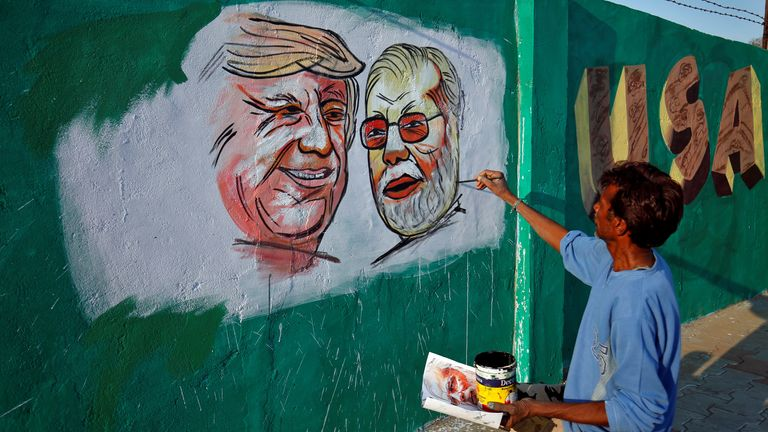 A man painting a picture of Donald Trump and Narendra Modi along the route the two men will take