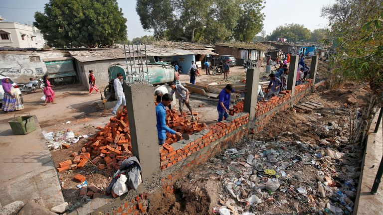 Construction workers building the wall in the slum area