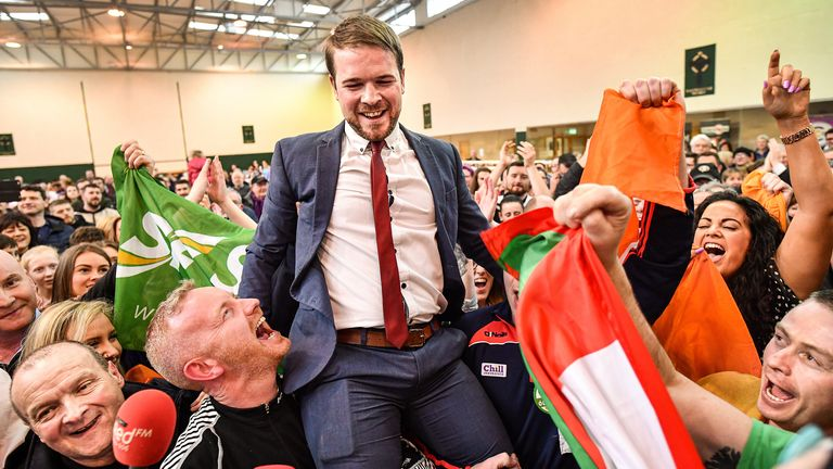Sinn Fein's Donnchadh Ó Laoghaire (C) celebrates being the first TD elected to the 33rd Dáil, topping the poll ahead of Micheál Martin, Simon Coveney and Michael McGrath at Nemo Rangers GAA Club on February 9, 2020 in Cork, Ireland