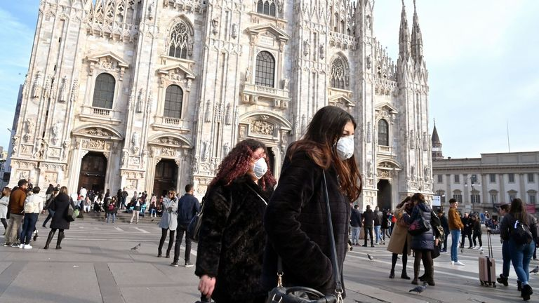 Women wearing a respiratory mask walks across Piazza del Duomo in central Milan on February 23, 2020. - Tens of thousands of Italians prepared for a weeks-long quarantine in the country's north on February 23 as nerves began to fray among the locals faced with new lockdown measures