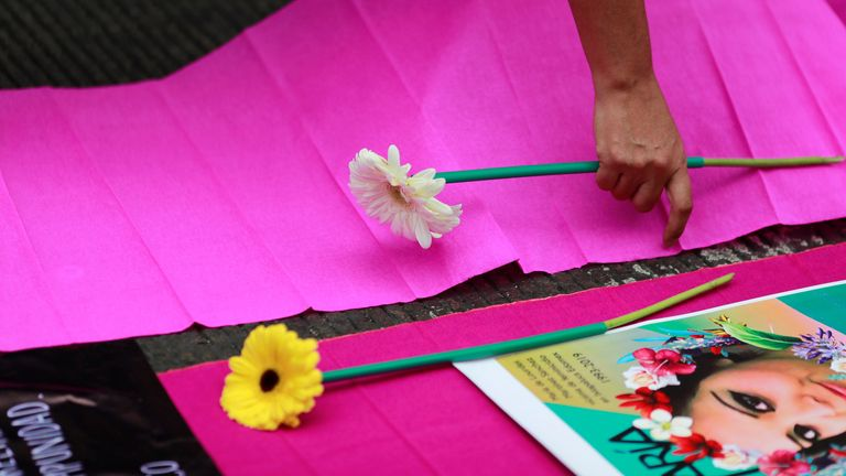 A protester lays flowers on a poster during a protest against gender-based violence in downtown of Mexico City, Mexico, February 14, 2020