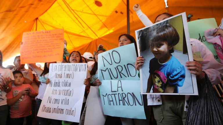 Protesters hold placards at the home of Fatima Cecilia Aldrighett