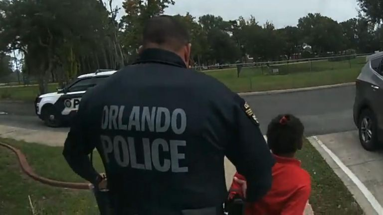 Six-year-old Kaia Rolle is led away with her hands bound by cable ties
