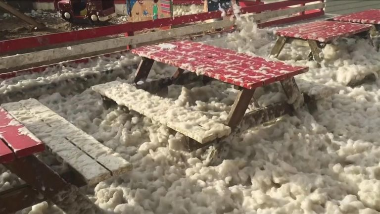 Foam washed ashore by stormy weather covering a cafe's outside seating in Bude, England