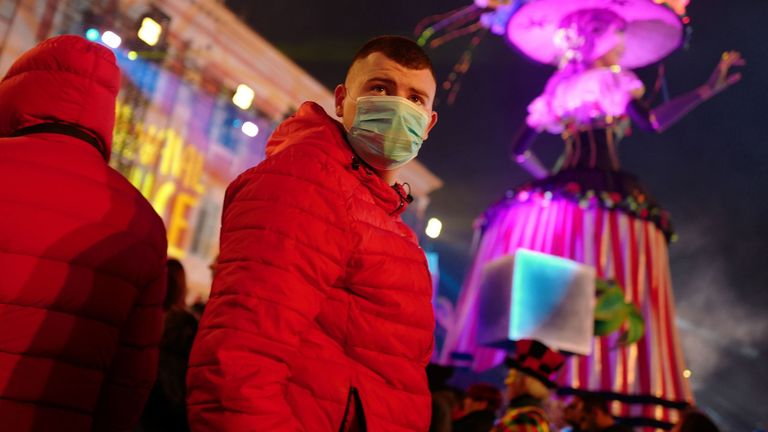 Revellers wear masks to protect themselves from the COVID-19 illness as they attend the Nice carnival on the french riviera city of Nice, on February 25, 2020