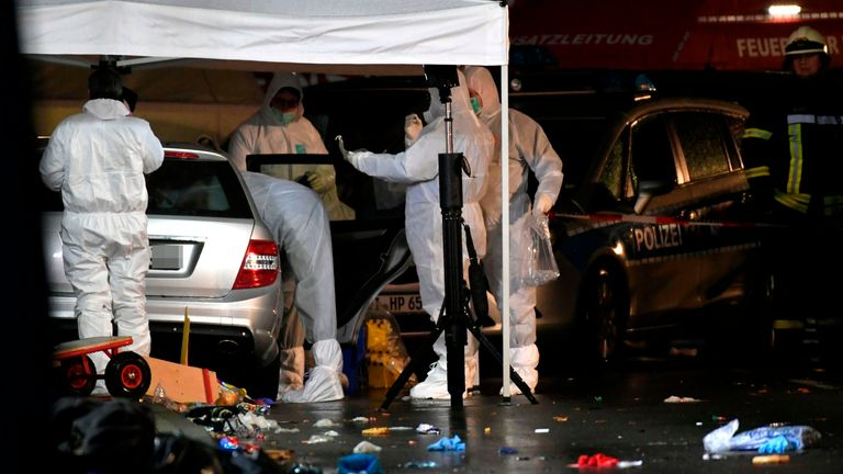 Police officers investigate the car of the man who drove into a carnival parade in Volksmarsen, Germany
