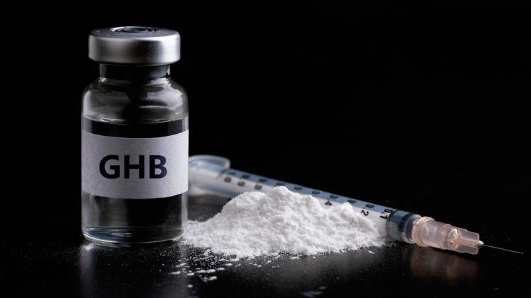 Bottle of GHB with a syringe in black background.Dangerous drug women