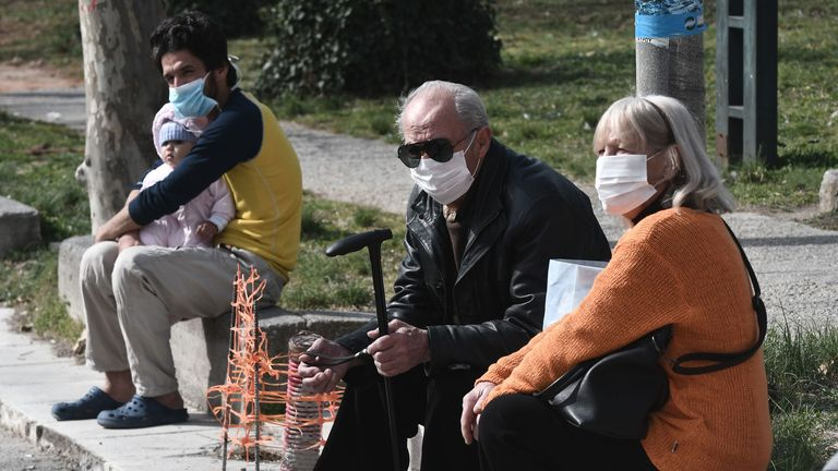 People with face masks sit outside a hospital in Thessaloniki, Greece