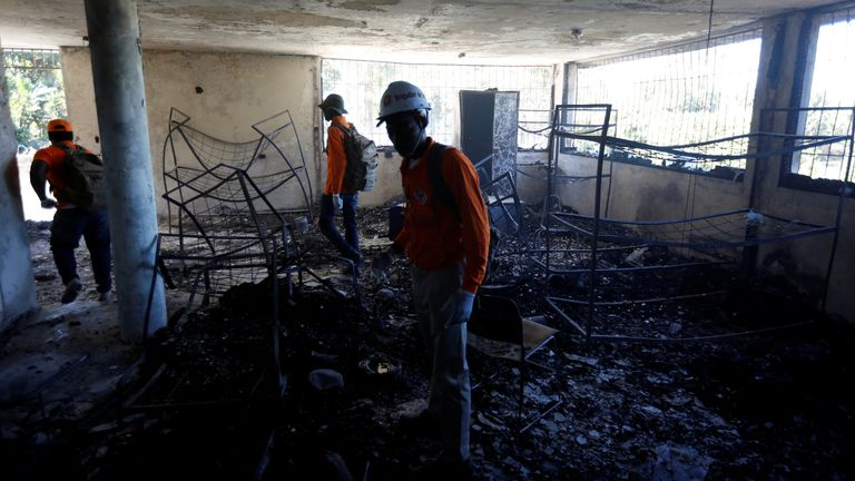 Civil protection workers inspect a bedroom at the orphanage after the fire
