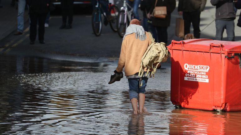 A woman wades through flooded streets in Hereford