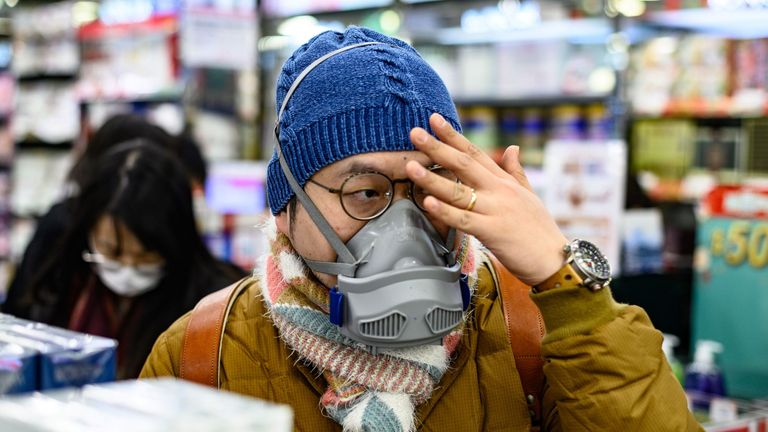 A man is seen with his face covered while buying packets of masks in a Hong Kong pharmacy