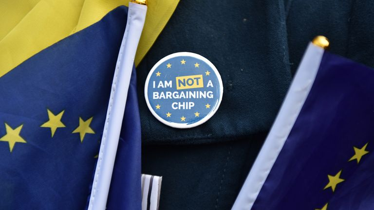 "A migrant worker wears a badge quoting ""I am NOT a bargaining chip"" outside the Houses of Parliament on January 15, 2019 in London, England"