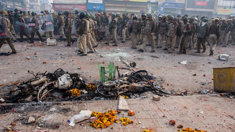 Indian police and paramilitary forces on a road in New Delhi destroyed in clashes over the citizenship act