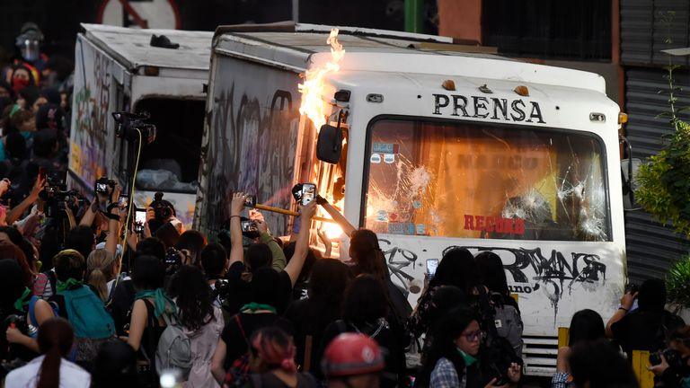 A press vehicle is set on fire as women march in Mexico City on February 14, 2020, to protest gender violence. - Several protests convened on Friday in the Mexican capital and other cities of the country after the murder of Ingrid Escamilla, 25, stabbed to death and then skinned by her partner in the north of Mexico City on February 9